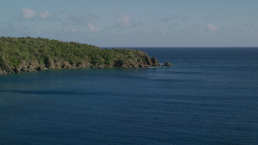 5k stock footage aerial video of a Tree covered rugged coast along blue waters of Great Lameshur Bay, St John Aerial Stock Footage | AX103_056