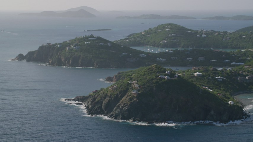 5k aerial video of a Hilltop and cliff top mansions along Caribbean blue waters, Cruz Bay, St John Aerial Stock Footage | AX103_060