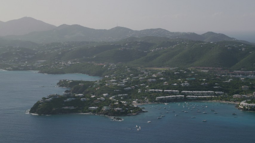 5k stock footage aerial video of Homes nestled in trees around Caribbean blue waters of the bay, East End, St Thomas Aerial Stock Footage | AX103_063