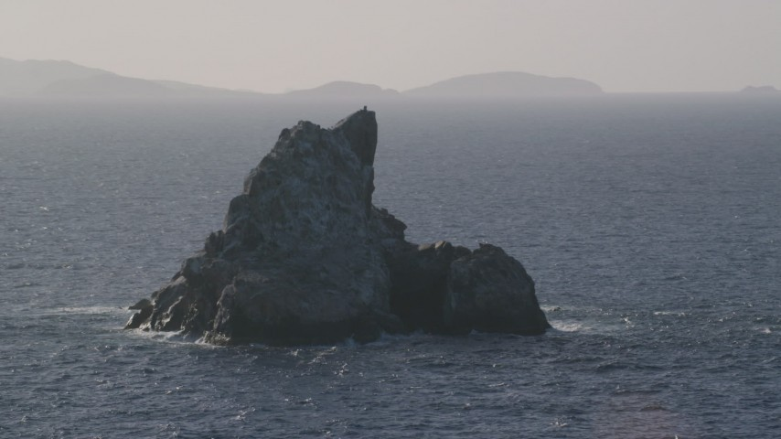5k stock footage aerial video of a Rock formation in Caribbean blue waters, St Thomas Aerial Stock Footage | AX103_081