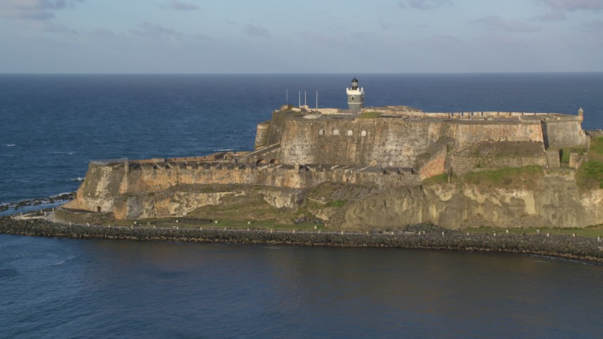 5k stock footage aerial video of Fort San Felipe del Morro along Caribbean blue waters, Old San Juan, sunset Aerial Stock Footage | AX104_007