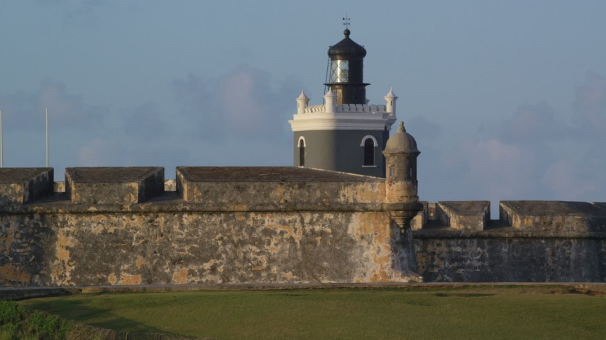 5k stock footage aerial video of Port San Juan Light and Fort San Felipe del Morro, Old San Juan, sunset Aerial Stock Footage | AX104_023