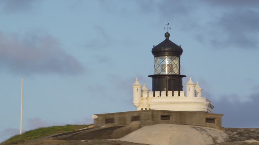 5k stock footage aerial video of Port San Juan Light atop Fort San Felipe del Morro, Old San Juan, sunset Aerial Stock Footage | AX104_025