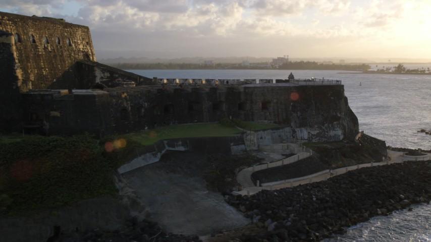 5K stock footage aerial video of Fort San Felipe del Morro and blue ocean waters, Old San Juan, sunset Aerial Stock Footage | AX104_029