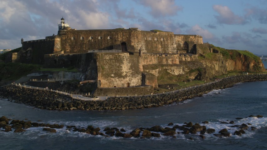 5k stock footage aerial video of Fort San Felipe del Morro along calm ocean waters, Old San Juan, sunset Aerial Stock Footage | AX104_030