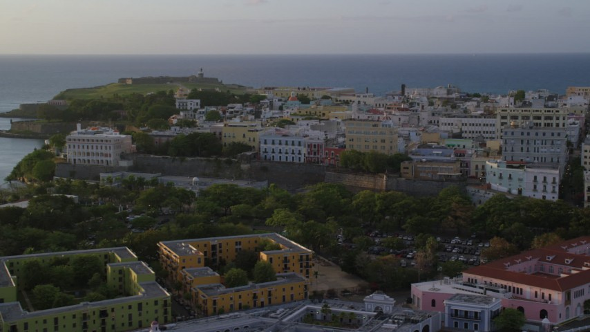 5k stock footage aerial video of La Fortaleza among Caribbean buildings, Old San Juan, sunset Aerial Stock Footage | AX104_034