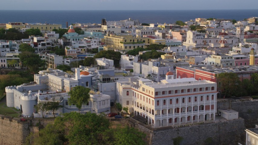 5k stock footage aerial video of La Fortaleza among neighboring buildings, Old San Juan, sunset Aerial Stock Footage | AX104_038
