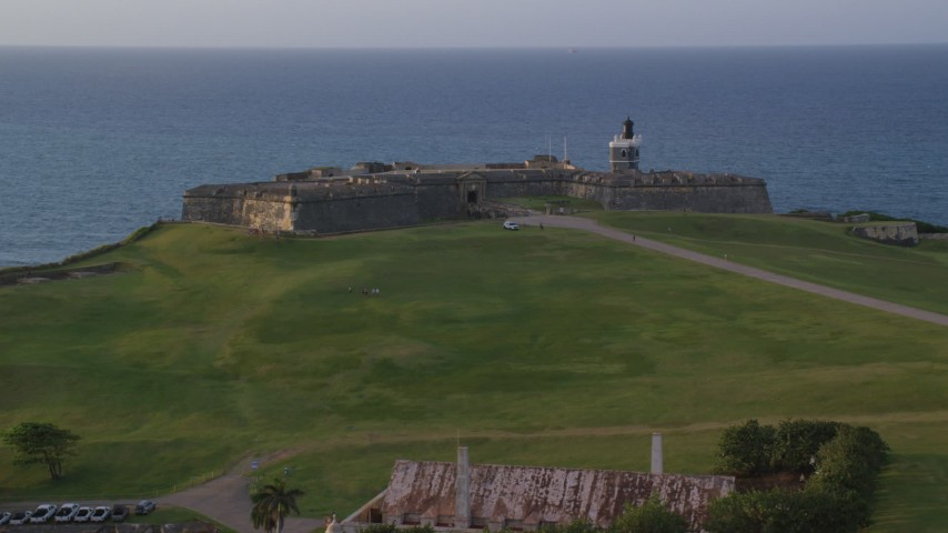 5k stock footage aerial video of Fort San Felipe del Morro overlooking the ocean, Old San Juan sunset Aerial Stock Footage | AX104_042