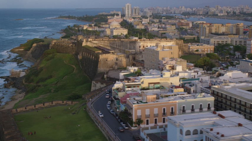 5k stock footage aerial video of Fort San Cristobal along the ocean, Old San Juan sunset Aerial Stock Footage | AX104_044