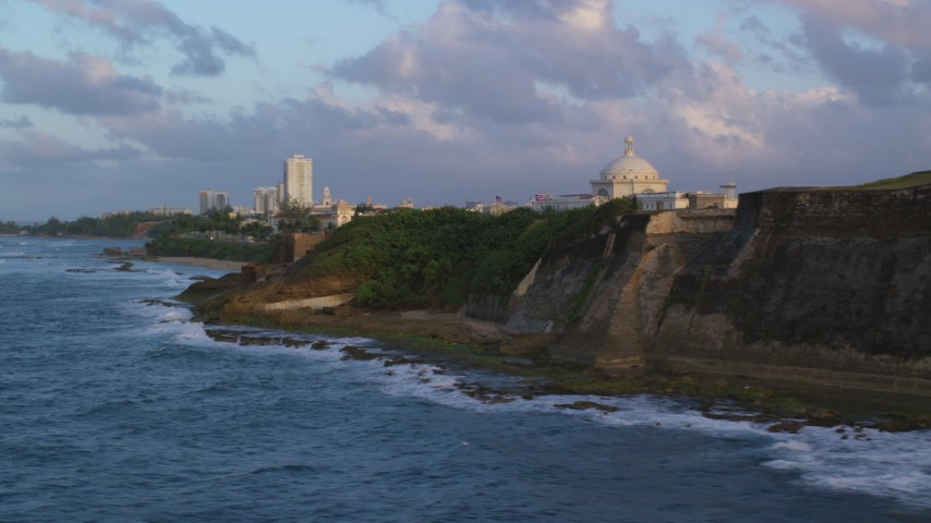 5k stock footage aerial video of San Juan Capitol Building along the ocean, Old San Juan Puerto Rico, sunset Aerial Stock Footage | AX104_045