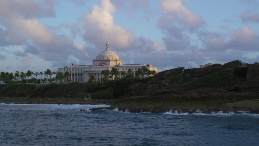 5k stock footage aerial video of Oceanfront San Juan Capitol Building, Old San Juan Puerto Rico, sunset Aerial Stock Footage | AX104_046