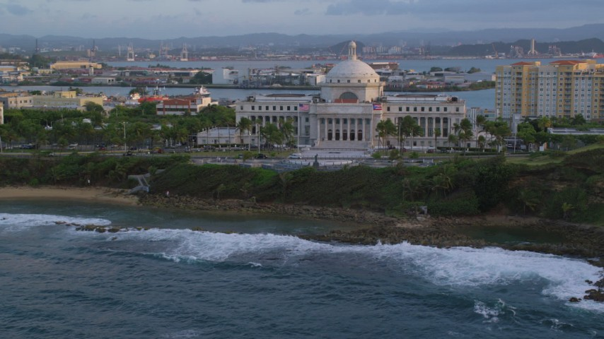 5k stock footage aerial video of the San Juan Capitol Building along the ocean, Old San Juan, Puerto Rico, sunset Aerial Stock Footage | AX104_051