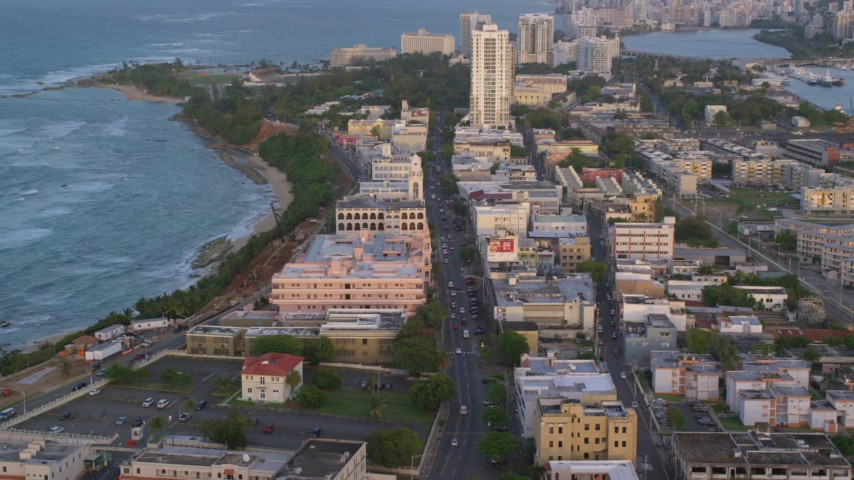 5k stock footage aerial video Following Avenida Juan Ponce de Leon through buildings, Old San Juan, Puerto Rico, sunset Aerial Stock Footage | AX104_053