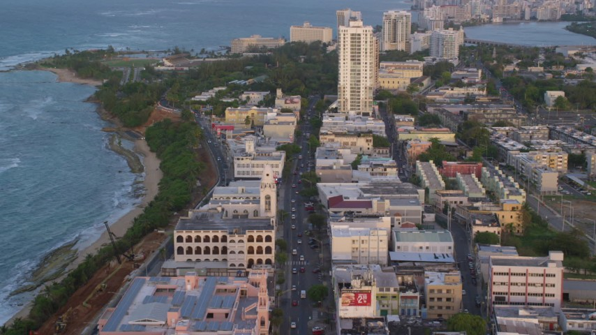 5k stock footage aerial video of Avenida Juan Ponce de Leon through buildings, Old San Juan, Puerto Rico, sunset Aerial Stock Footage | AX104_054