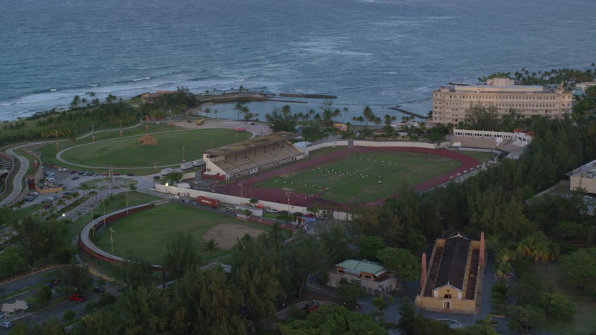 5k stock footage aerial video of Estadio Sixto Escobar stadium oceanside, San Juan, Puerto Rico, sunset Aerial Stock Footage | AX104_057