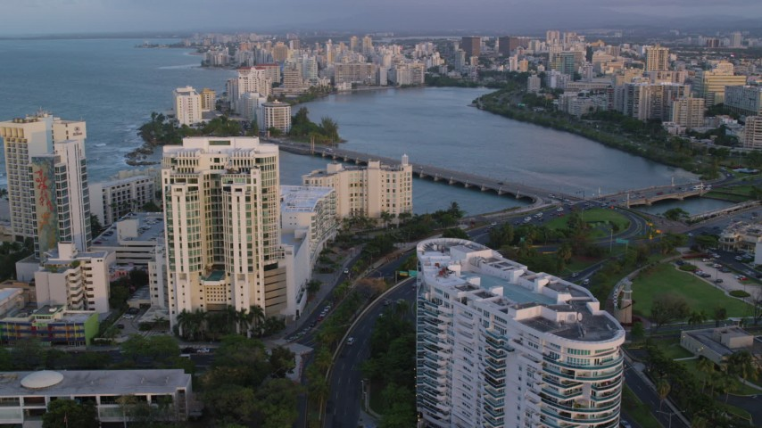 5k aerial video of Avenida Ashford bridge and high-rises, San Juan, Puerto Rico, sunset Aerial Stock Footage | AX104_058