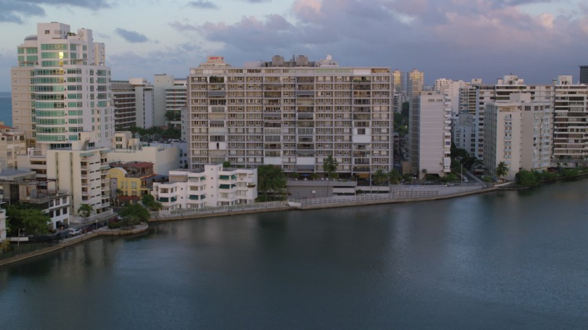 5k stock footage aerial video of Hotels along Caribbean blue waters, San Juan, Puerto Rico sunset Aerial Stock Footage | AX104_061