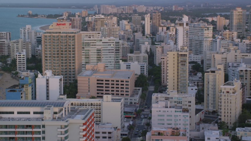 5k stock footage aerial video of Oceanside Caribbean hotels and apartment buildings, San Juan, Puerto Rico sunset Aerial Stock Footage | AX104_062