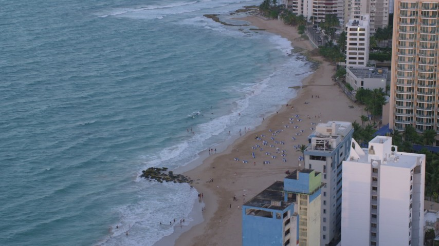 5k stock footage aerial video of a Caribbean beach and turquoise waters, San Juan, Puerto Rico, sunset Aerial Stock Footage | AX104_063