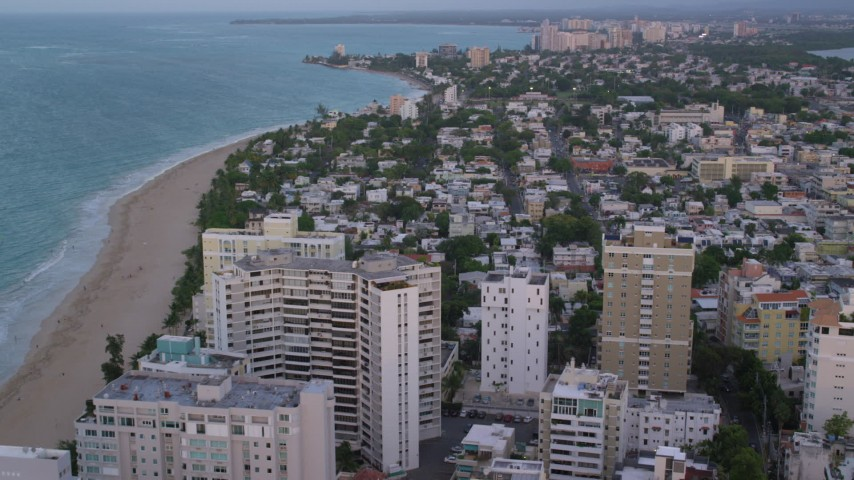 5k stock footage aerial video of Coastal neighborhoods, Caribbean beach and turquoise waters, San Juan, Puerto Rico, sunset Aerial Stock Footage | AX104_066
