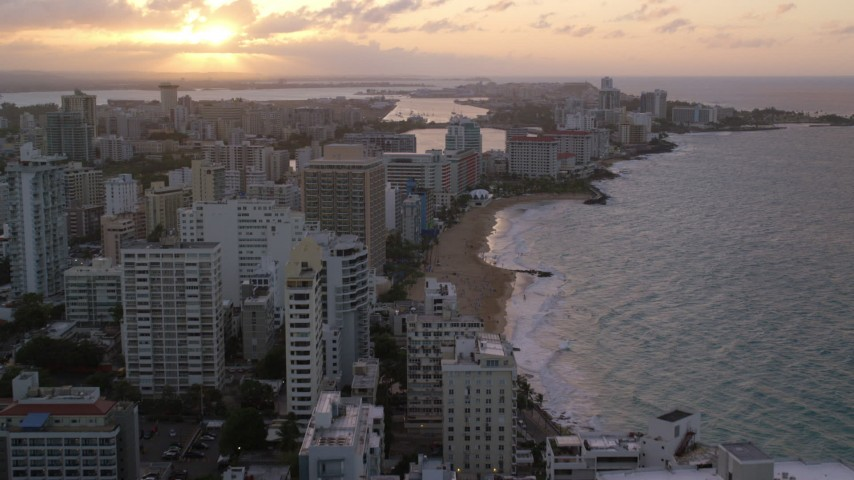 5k aerial video of Beachfront hotels and ocean waters, San Juan, Puerto Rico, sunset Aerial Stock Footage AX104_068