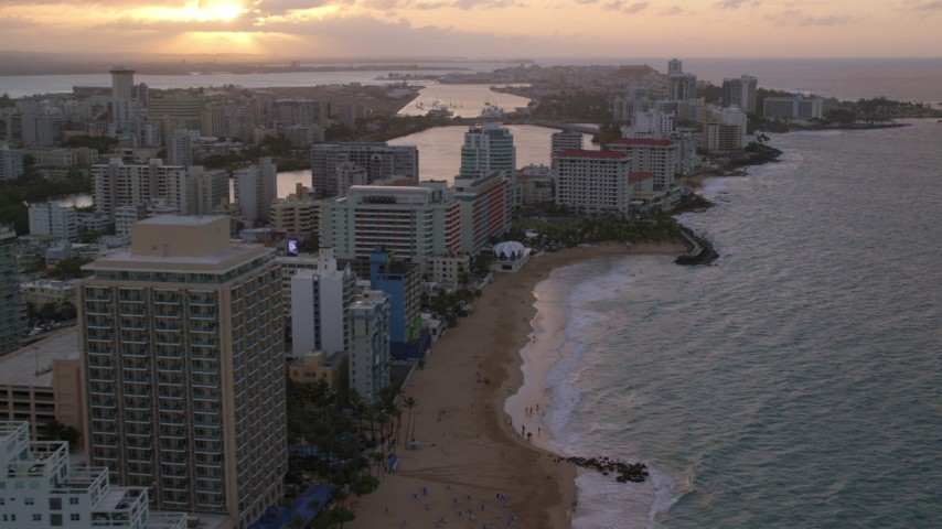 5k stock footage aerial video of Beachfront Caribbean hotels along the ocean, San Juan, Puerto Rico, sunset Aerial Stock Footage | AX104_069