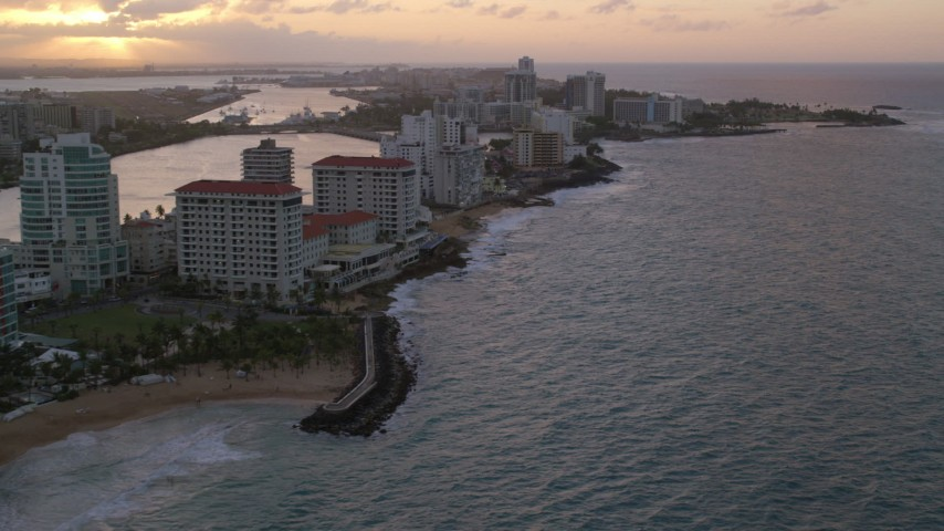 5k aerial video of Beachfront Caribbean hotels along the ocean, San Juan, Puerto Rico, sunset Aerial Stock Footage | AX104_070