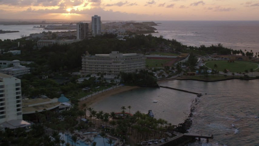 5k stock footage aerial video of the Oceanfront Normandie Hotel and Estadio Sixto Escobar, San Juan Puerto Rico, sunset Aerial Stock Footage AX104_073 | Axiom Images