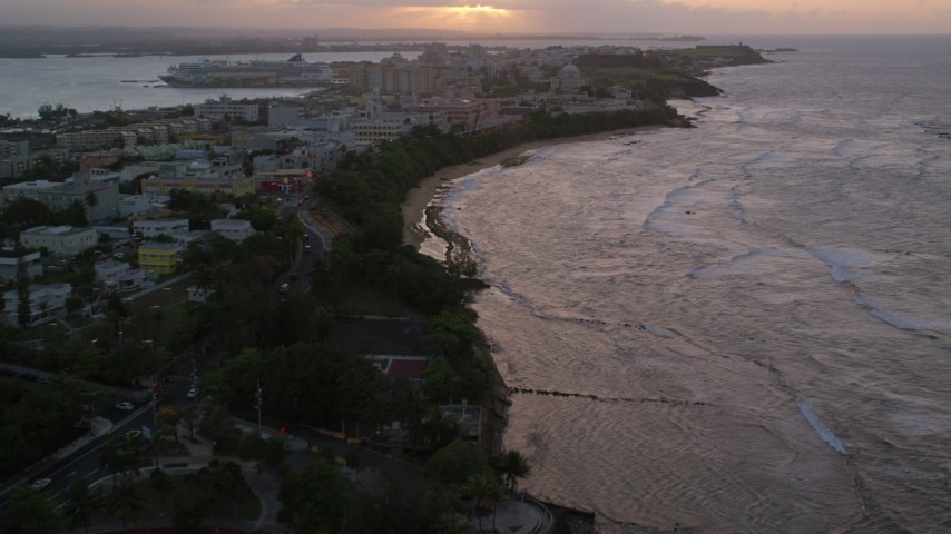 5k stock footage aerial video of Caribbean buildings near the beach and ocean, Old San Juan, Puerto Rico, sunset Aerial Stock Footage | AX104_075