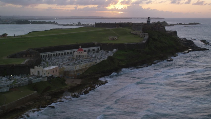 5K stock footage aerial video Approaching Fort San Felipe del Morro and lighthouse, Old San Juan, sunset Aerial Stock Footage | AX104_080