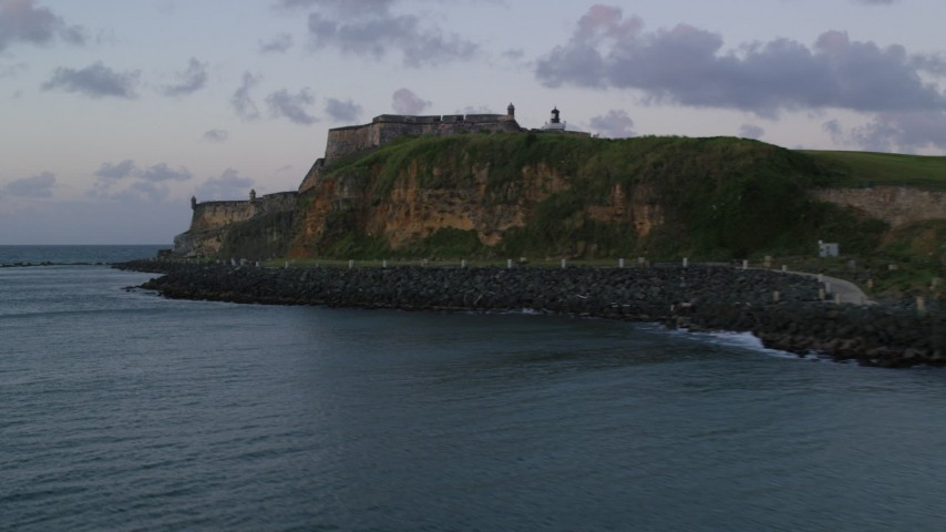 5k stock footage aerial video Flying along the walls of Fort San Felipe del Morro, Old San Juan, twilight Aerial Stock Footage | AX104_081