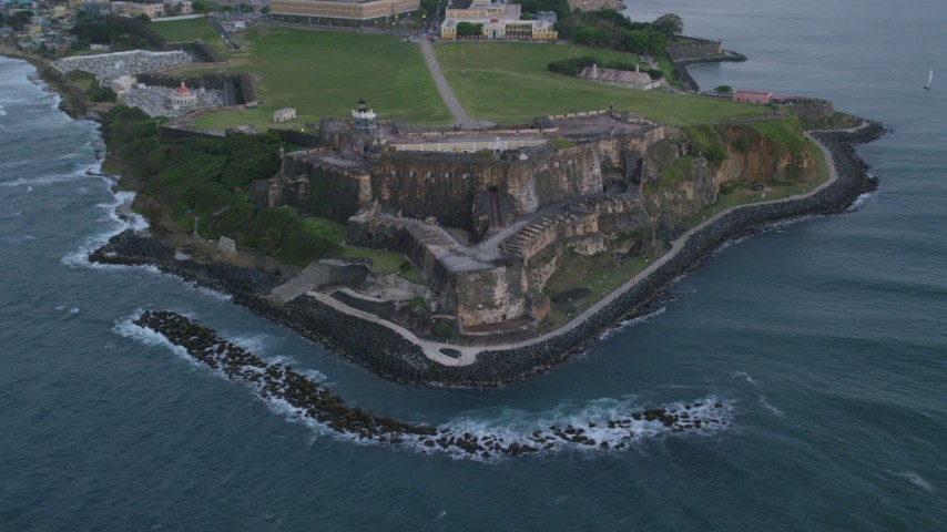5k stock footage aerial video of Fort San Felipe del Morro along Caribbean blue waters, Old San Juan, twilight Aerial Stock Footage | AX104_084