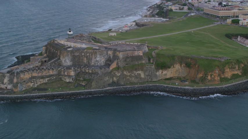 5k stock footage aerial video of Fort San Felipe del Morro and Caribbean blue ocean waters, Old San Juan, twilight Aerial Stock Footage | AX104_085