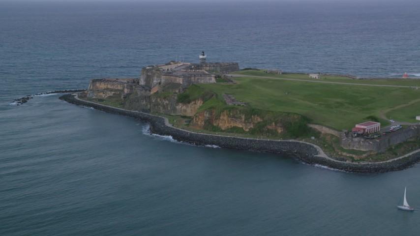 5k stock footage aerial video of Fort San Felipe del Morro and Caribbean blue ocean waters, Old San Juan, twilight Aerial Stock Footage | AX104_086