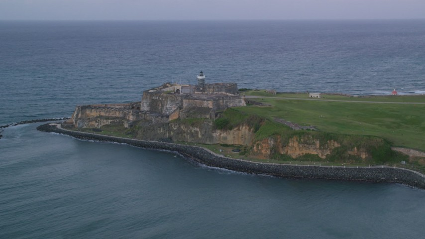 5k stock footage aerial video of Fort San Felipe del Morro and Caribbean blue ocean waters, Old San Juan, twilight Aerial Stock Footage | AX104_087