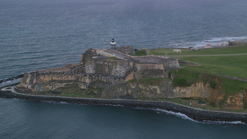 5k stock footage aerial video of Fort San Felipe del Morro along Caribbean blue ocean waters, Old San Juan, twilight Aerial Stock Footage | AX104_088