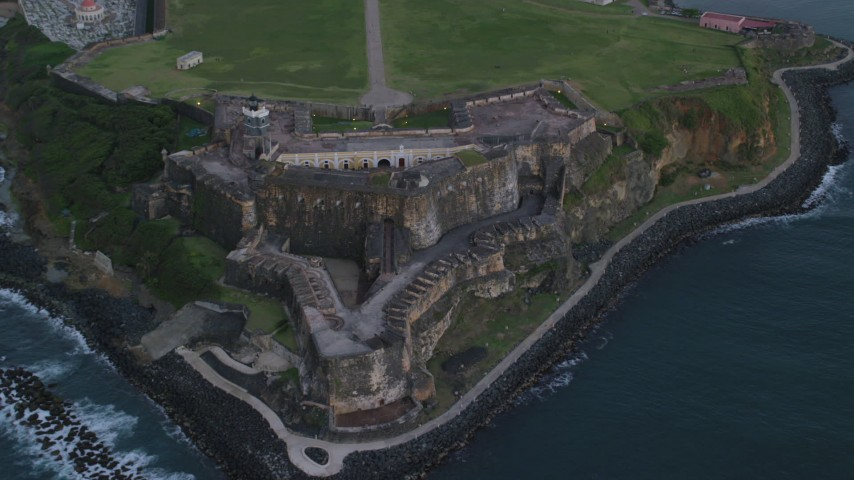 5k stock footage aerial video of Fort San Felipe del Morro along Caribbean blue ocean waters, Old San Juan, twilight Aerial Stock Footage | AX104_090