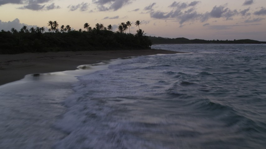 5K stock footage aerial video Flying low along a Caribbean beach and ocean waters, Dorado, Puerto Rico, twilight Aerial Stock Footage | AX104_105