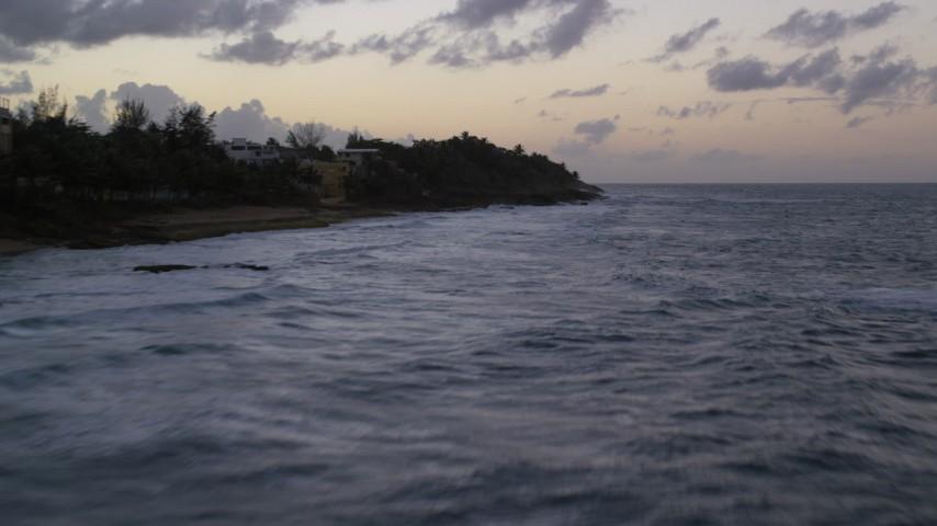 5k stock footage aerial video Flying low over ocean water along coastal homes, Dorado, Puerto Rico, twilight Aerial Stock Footage | AX104_107