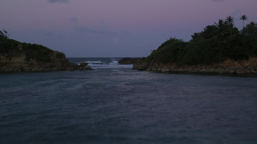 5K stock footage aerial video Flying over ocean and through a gap in the coast, Dorado, Puerto Rico, twilight Aerial Stock Footage | AX104_123