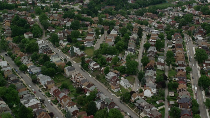 5K stock footage aerial video tilting up from homes to reveal skyscrapers, Downtown Pittsburgh, Pennsylvania Aerial Stock Footage | AX105_075