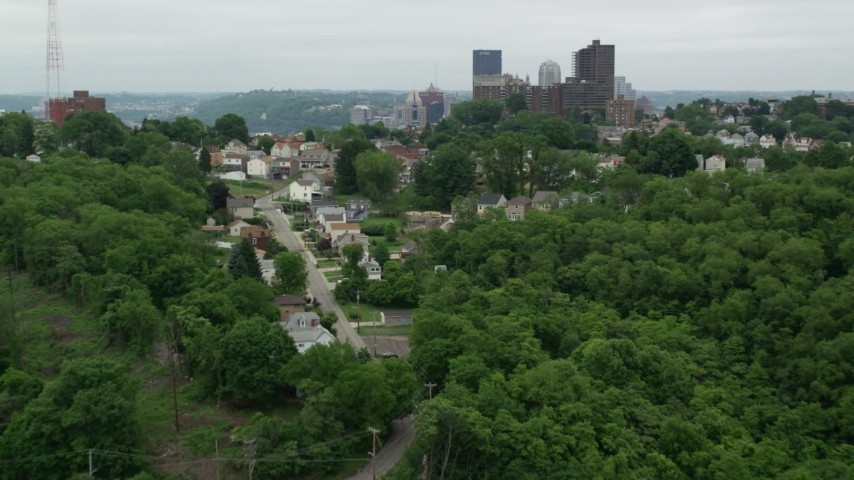5K stock footage aerial video of hillside homes revealing downtown skyscrapers, Downtown Pittsburgh, Pennsylvania Aerial Stock Footage | AX105_120