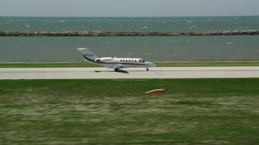 5K stock footage aerial video tracking Private Jet Taking Off from Cleveland Burke Lakefront Airport, Ohio Aerial Stock Footage AX106_269