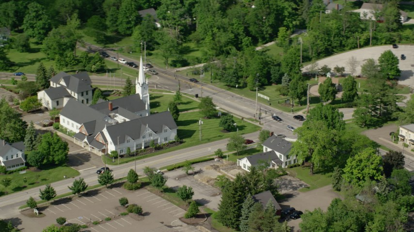 5K aerial video flying by a church along a busy road, Aurora, Ohio Aerial Stock Footage | AX107_075