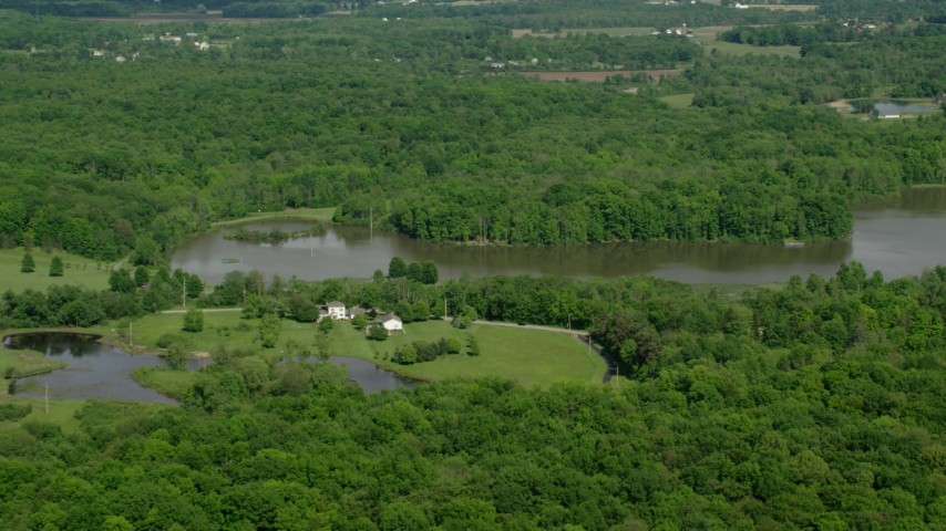 5K aerial video of isolated lakeside home surrounded by trees, Aurora, Ohio Aerial Stock Footage | AX107_076