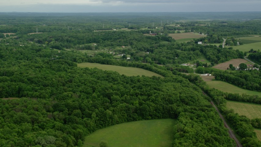 5K stock footage aerial video flying over forests toward rural homes, East Palestine, Ohio Aerial Stock Footage | AX107_111