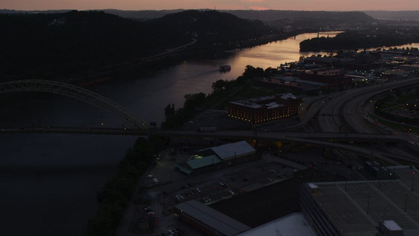 4K stock footage aerial video of an office building and warehouse along Ohio River, Pittsburgh, Pennsylvania, twilight Aerial Stock Footage | AX108_089