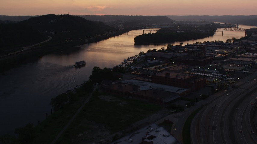 4K stock footage aerial video approaching warehouses along Ohio River, Pittsburgh, Pennsylvania, twilight Aerial Stock Footage | AX108_090