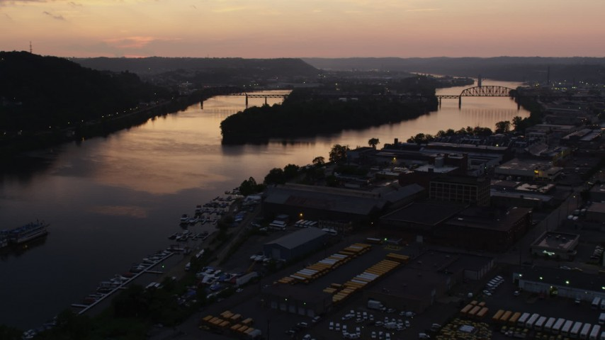 4K stock footage aerial video flying by warehouses toward Brunot Island, Pittsburgh, Pennsylvania, twilight Aerial Stock Footage | AX108_091