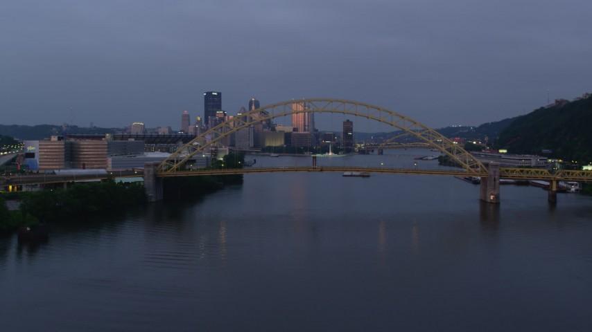 4K stock footage aerial video of Downtown skyline seen through West End Bridge, Pittsburgh, Pennsylvania, twilight Aerial Stock Footage | AX108_093
